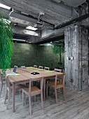 Konferenzraum in einem Loft mit Betonstützen, einem Konferenztisch aus hellem Holz und einem hellen Holzdielenboden