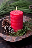 Red pillar candle with pinecones and pine twigs
