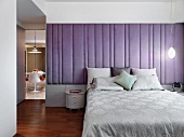 Elegant modern bedroom with purple padded wall