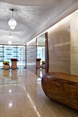 Long marble hallway with double glass doors at end