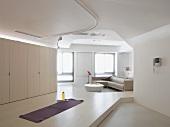 Podeste und Schienen an Decke definieren Bereiche im offenen Wohnraum