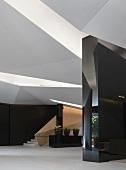 Eingangshalle mit gefaltetem Deckenelementen und dreidimensionalen Wänden mit polierten schwarzen Steinfliesen