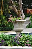 Antik griechische Vase im Blumenbeet und Blick auf Pool und Treppenanlage im Garten