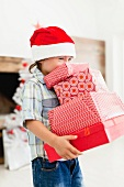Boy in Santa hat with Christmas gifts