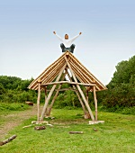 Man cheering on roof of log hut