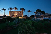 Front exterior Mediterranean style home at dusk