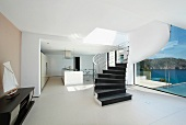 Spiral staircase through modern home with ocean view