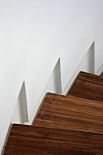 Detail wooden staircase along white wall