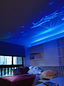 Underwater world on mystic, blue-lit ceiling of child's bedroom with teddy bears on bed