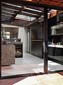 Designer kitchen with stone-clad kitchen counter below glass roof and fitted kitchen behind sliding door