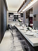 Classic modern dining area with festively set white table and designer chairs of acrylic glass