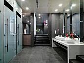 Grauweisses Interieur im klassisch modernen Toiletten-Vorraum mit Milchglastüren und Blumenschmuck zwischen ovalen Waschschüsseln
