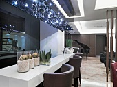 Classic modern lounge area and counter with leather stools below glittering chandeliers in blue light box of acrylic glass