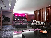 Extensive seating area with sofas, modern bar with hot pink light boxes and concert grand in classic modern hotel lounge