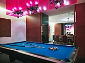 Pool table with cornflower blue felt set up for game below chandeliers in hot pink light boxes