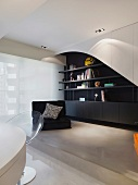 Modern living room - black low armchair in front of black and white built-in shelves on a platform