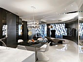Contemporary living room with a dining table and white shell chairs on a white high gloss floor and illuminated wall