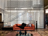 Printed pane of glass in front of stairway and modern couch upholstered in orange velvet in an open living room