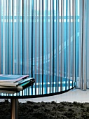 Round table with reflective surface in front of a mirror with a see-through curtain with a striped pattern
