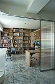 Wohnraum mit Steinboden und Blick durch offene Glasschiebetür in Arbeitsbereich