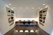 Arbeitsbereich mit Schalenstühlen auf hochglänzendem Steinboden und futuritische Raumteiler mit integriertem Regal