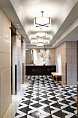 Elegant gestalteter Gang - Hängelampen mit Glasschirm über Steinboden mit schwarz weißem Muster