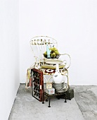 Stack of flea market finds around and on vintage metal chair in corner of room
