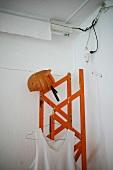 Vest and pumpkin helmet on red wooden lattice girder in corner of room