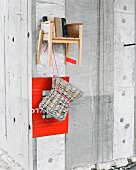 Stool made from newspaper in front of red photo mount and child's stool made from reclaimed wood hanging on concrete wall