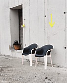 Vintage shell chairs with leather covers against concrete wall