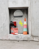 Pouffes made from bundled old cloths and lamp made from old buckets in niche of concrete wall