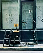 Various vintage-style chairs and standard lamp in front of old shop