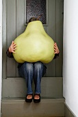 Woman sitting on front door step with huge model pear on lap