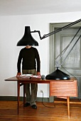 Giant, black retro desk lamp on fifties-style desk with man in background