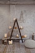 Lit candles on home-made shelving with white shelves in rustic atmosphere