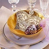 Christmas decorations in gold bowl on place setting with crystal glasses