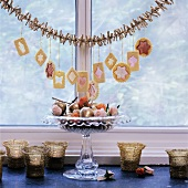 Christmas biscuits hanging from garland above dish of decorations on window sill