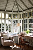 Bright home office in tasteful, country-house style with cushioned window seat in front of corner lattice glazing in window bay below wood-clad, hipped roof