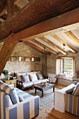 Seating area with striped sofas in tasteful country house style below rustic roof beams in historical building