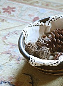Fir cones and balls of twigs in dish with crochet-edged doily on kilim rug