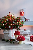 Decorated Christmas tree and decorative mushrooms on floor next to white table in front of stacked presents on wall console
