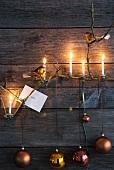 An Holzwand aufgehängte Weihnachtskugeln und brennende Kerzen an Zweig im Kerzenhalter