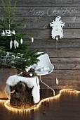 Lichterkette schlingt sich um Baumstumpf mit Fell und geschmücktem Weihnachtsbaum vor Vintage Holzwand mit Kuckucksuhr