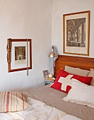 Red cushion with white cross on simple bed in corner of room with framed photos on walls