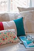 Verschiedene Kissen mit Streifen und Blumenmuster neben aufgeschlagenem Buch auf Tagesbett