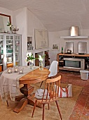 Round wooden table, simple kitchen chair and Bauhaus shell chair in Mediterranean dining room with kitchenette