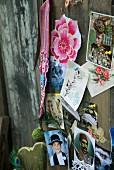 Kartensammlung und Blumenmotiven, angepinnt an eine alte Holzwand