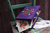 Collection of post cards in painted and decorated wooden box on vintage chair