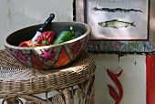 Colourful ceramic bowl of vegetables on wicker stool; framed picture of fish on wall