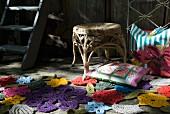 In verschiedenen Farben gehäkelte Blumenmotive und buntes Dekokissen vor Flechthocker auf Holzboden